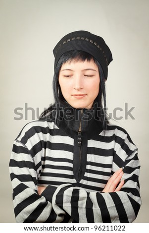 Young woman wearing in winter clothing: cap and striped sweater. Winter fashion