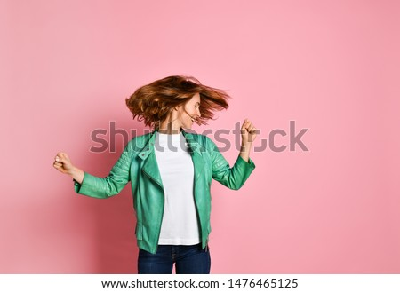 young woman wearing jeans and a jacket is shaking her head with her hair. The concept of joy, happiness, joy, fun #1476465125