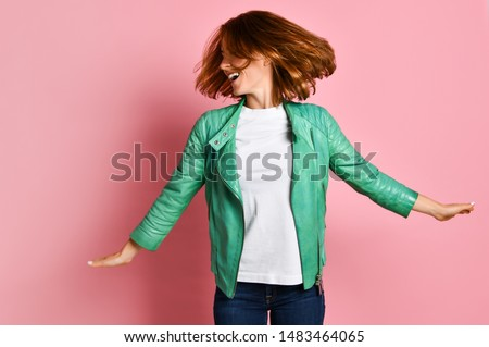 young woman wearing jeans and a jacket is shaking her head with her hair. The concept of joy, happiness, joy, fun #1483464065
