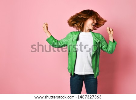 young woman wearing jeans and a jacket is shaking her head with her hair. The concept of joy, happiness, joy, fun #1487327363