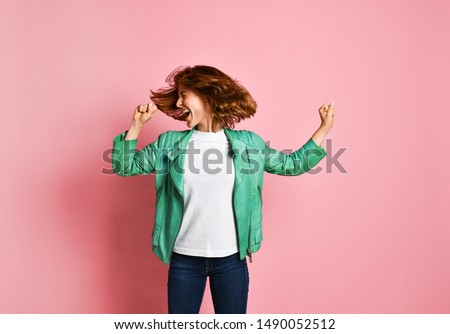 young woman wearing jeans and a jacket is shaking her head with her hair. The concept of joy, happiness, joy, fun #1490052512