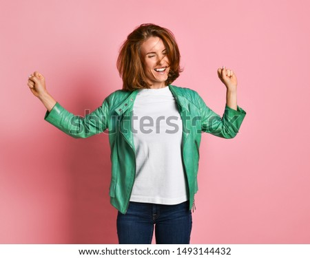 young woman wearing jeans and a jacket is shaking her head with her hair. The concept of joy, happiness, joy, fun #1493144432