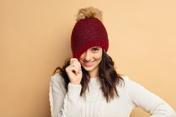 young woman wearing knitted pullover over beige background. Happy smiling girl in winter hat