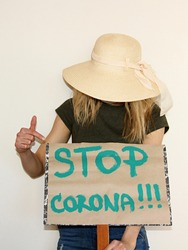young woman wearing mask to protect from coronavirus and holding board with text