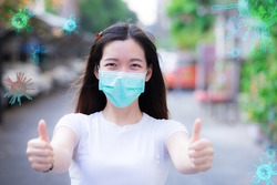 Young woman wearing medical face mask show thumbs up for good and happy at home. Coronavirus disease. Stay home. Social distancing. New normal behavior. Coronavirus Covid-19 pm2.5. Work at home.