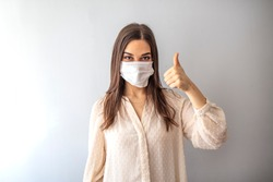Young woman wearing medical face mask, studio portrait. Woman Wearing Protective Mask and Showing OK sign. Woman wearing surgical mask for corona virus.