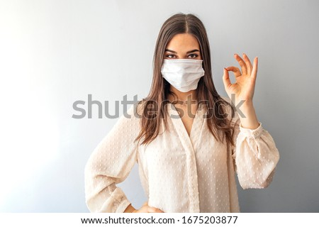 Photo of Young woman wearing medical face mask, studio portrait. Woman Wearing Protective Mask and Showing OK sign. Woman wearing surgical mask for corona virus
