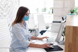 Young woman wearing medical mask in office. Protection employees on workplace. Girl working at reception indoors. Social distancing in public place, disease prevention during quarantine, staff safety.
