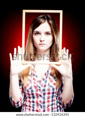 Young woman wearing plaid shirt holding wooden frame around her face