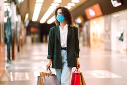 Young woman wearing protection face mask against coronavirus after shopping  in the mall. Purchases, shopping, lifestyle concept. Covid-2019.