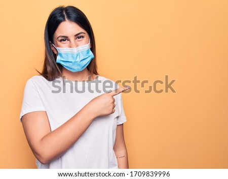 Young woman wearing protection mask for coronavirus disease over yellow background smiling cheerful pointing with hand and finger up to the side