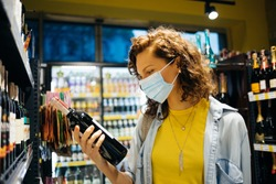 Young woman wearing protective face mask chooses wine in grocery store.