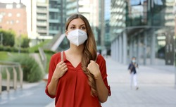 Young woman wearing protective mask KN95 FFP2 walking in modern city street. Student girl with face mask against Coronavirus Disease 2019 (COVID-19).