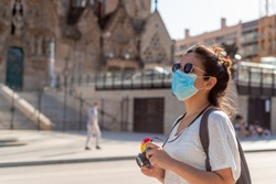 young woman wearing protective mask taking pictures with camera and doing tourists things in front of landmark monuments in barcelona, spain. Tourism faces challenges due to the coronavirus pandemic