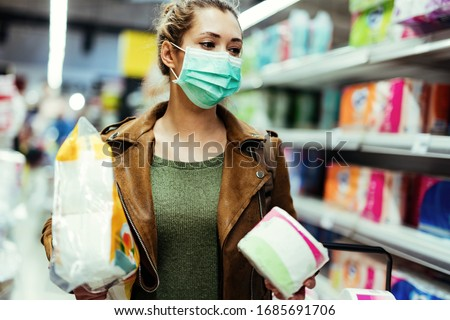 Young woman wearing protective mask while shopping toilet paper in the store during virus epidemic.