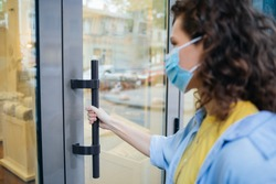 Young woman wearing protective medical mask holds on to the handle and opens the door when entering store.