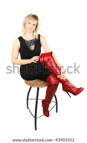 Young woman wearing red boots and black little dress sitting on the high chair  isolated on the white.