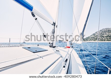 Young woman wearing red shorts, sitting on deck under sails on yacht bow and enjoying wonderful view to cliffs in peaceful sea during summer sailing holidays - yacht charter concept
