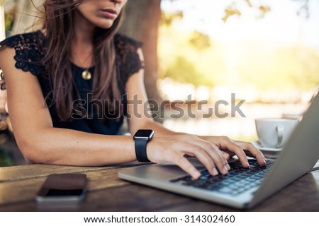 Young woman wearing smartwatch using laptop computer. Female working on laptop in an outdoor cafe.