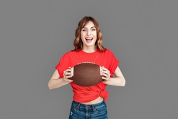 Young woman wearing sports clothes studio standing isolated on grey background holding american football ball looking camera laughing cheerful