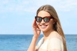 Young woman wearing stylish sunglasses with reflection of palm trees near sea