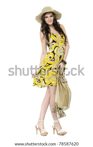 young woman wearing summer dress posing in a hat