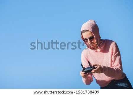 Young woman wearing sunglasses and hoodie holding a remote control, controls, controls are not visible in the frame drone. A woman carefully looks into the distance against a blue sky. Copyspace.