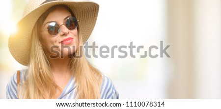 Young woman wearing sunglasses and summer hat holding blank advertising banner, good poster for ad, offer or announcement, big paper billboard #1110078314