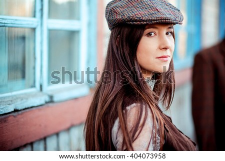 young woman wearing tweed flat...