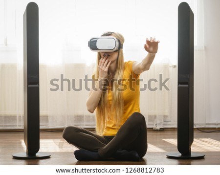 Young woman wearing virtual reality goggles vr box with arms outstretched sitting on floor in living room, listening to music. Connection, technology, new generation and progress concept. #1268812783