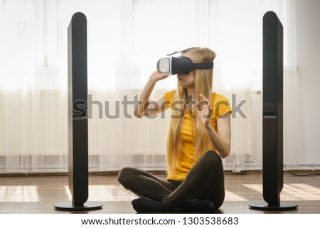 Young woman wearing virtual reality goggles vr box with arms outstretched sitting on floor in living room, listening to music. Connection, technology, new generation and progress concept. #1303538683