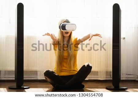 Young woman wearing virtual reality goggles vr box with arms outstretched sitting on floor in living room, listening to music. Connection, technology, new generation and progress concept. #1304554708