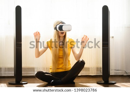 Young woman wearing virtual reality goggles vr box with arms outstretched sitting on floor in living room, listening to music. Connection, technology, new generation and progress concept. #1398023786