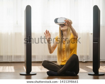 Young woman wearing virtual reality goggles vr box with arms outstretched sitting on floor in living room, listening to music. Connection, technology, new generation and progress concept. #1415398661