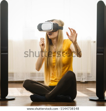 Young woman wearing virtual reality goggles vr 3d box sitting on floor in living room, listening to music. Connection, technology, new generation and progress concept. #1144738148