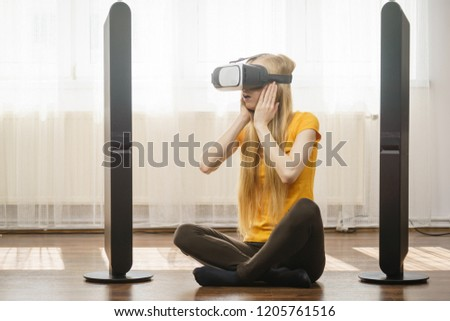 Young woman wearing virtual reality goggles vr 3d box sitting on floor in living room, listening to music. Connection, technology, new generation and progress concept. #1205761516