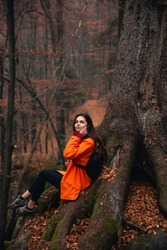 Young woman wearing warm orange jacket sitting on the rock in the autumn forest. Misty landscape with mossy rocks. Cute smiley woman in the nature. Autumn forest hiking
