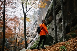 Young woman wearing warm orange sweater in the autumn forest. Misty landscape with mossy rocks. Cute smiley woman in the nature. Autumn forest hiking