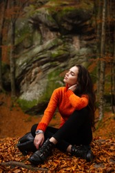 Young woman wearing warm orange sweater sitting on a fallen autumn leaves in the autumn forest. Misty landscape with mossy rocks. Cute smiley woman in the nature. Autumn forest hiking