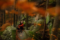 Young woman wearing warm orange sweater sitting on the rock in the autumn forest. Misty landscape with mossy rocks. Cute smiley woman in the nature. Autumn forest hiking
