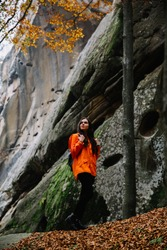 Young woman wearing warm orange sweater standing on a fallen autumn leaves in the autumn forest. Misty landscape with mossy rocks. Cute smiley woman in the nature. Autumn forest hiking
