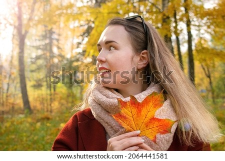 Young woman wearing warm scarf and coat is holding orange maple leaf and smiling in the park. Enjoying sunny weather