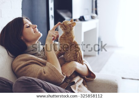 Young woman wearing warm sweater is resting with a cat on the armchair at home one autumn day