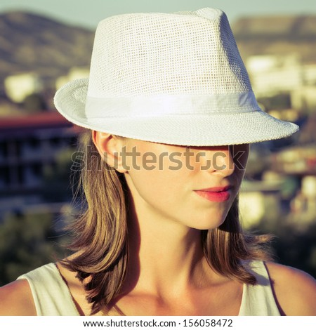 Young woman wearing white hat