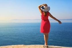 Young woman, wearing white hat and red dress, enjoying sea view.