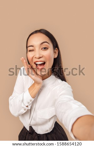 Young woman wearing white shirt with dark long hair standing isolated on bage background taking selfie photo winking to camera posing smiling playful