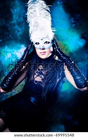 young woman wearing white venetian mask with feathers, black dress and long black gloves, studio shot