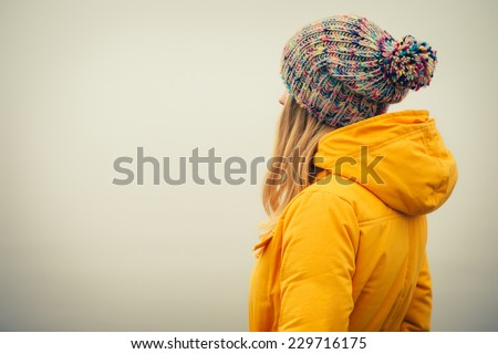 Young Woman wearing winter hat fashion clothing outdoor Travel Lifestyle and melancholy emotions concept foggy nature on background