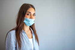 Young woman wears protective face mask, wrong way, incorrect wearing - masks should cover nose as well. How to NOT wear a mask. The wrong way to wear a mask on the chin and open nose