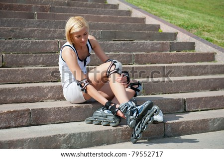 Young woman wears roller skates on the stairs